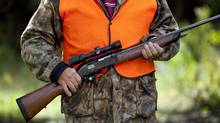 A rifle owner walks through a hunting camp near Ottawa on Sept. 15, 2010. (Sean Kilpatrick/THE CANADIAN PRESS)