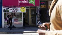 A person holds a mobile phone while walking by a Mobilicity store. (Michelle Siu For The Globe and Mail)