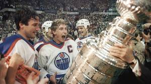 Edmonton Oilers captain Wayne Gretzky gets ready to hoist the Stanley Cup during the presentation in Edmonton, Alta., in this May 31, 1985, file photo. At left is Paul Coffey and at right is Mike Krushilnyski.