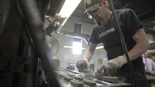 Rick Keleher places brake pad forms into a mould before being flash moulded at ABS Friction brake pad factory in Guelph Ontario on June 9, 2014. (PAWEL DWULIT/THE GLOBE AND MAIL)