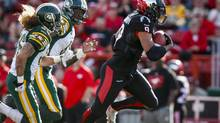 Edmonton Eskimos' Aaron Grymes, left, and Patrick Watkins, centre, chase Calgary Stampeders' Jon Cornish, during second half CFL football action in Calgary, Alta., Monday, Sept. 1, 2014. (Jeff McIntosh/THE CANADIAN PRESS)