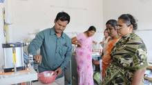 Entrepreneur Arunachalam Muruganantham inspects the production process with some of the owners of Mother Care. (STEPHANIE NOLEN/THE GLOBE AND MAIL)
