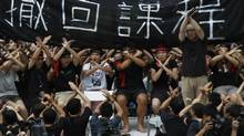 Protesters, who have gone on hunger strike since Saturday evening, gesture to show their refusal for the launch of national education in schools during a demonstration outside government headquarters in Hong Kong, on the first day of the new school term for primary and secondary schools, Sept. 3, 2012. (Bobby Yip/Reuters)