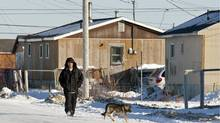 A man walks down the street in Attawapiskat, Ont., on Nov. 29, 2011. (Adrian Wyld/Adrian Wyld/The Canadian Press)