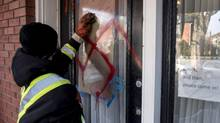 A graffiti removal worker cleans anti-Semitic graffiti, including a swastika, that was spray painted on the door of The Glebe Minyan and home of Rabbi Anna Maranta, on Tuesday, Nov. 15, 2016 in Ottawa. (Justin Tang/THE CANADIAN PRESS)
