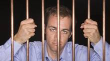 Businessman behind bars (Jupiterimages/Getty Images/Comstock Images)