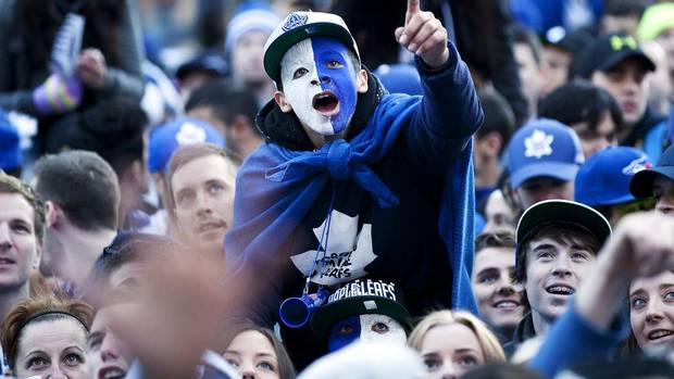A young fan is hoisted above a crowd at Toronto's Maple Leaf Square before the Toronto Maple Leafs take on the Boston Bruins for Game 7 of the first round of NHL Stanley Cup playoffs. (Michelle Siu for The Globe and Mail)