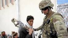 A U.S. soldier guides a Taliban militant, part of a group of a hundred Afghan Talibans, as he hands over his weapons as part of the Afghan government's reconciliation and reintegration program in Laghman province March 12, 2012. (PARWIZ/REUTERS/PARWIZ/REUTERS)