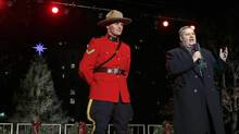 In this Nov. 29, 2012 file photo, Frank Corbett, then-Deputy Premier of Nova Scotia, is flanked by RCMP officer during the lighting of the City of Boston's Christmas tree in Boston. The annual gift by Nova Scotia of the tree is in honor of aid that Boston sent following the 1917 explosion of a munitions ship in Halifax harbor that killed more than 1,600. (Charles Krupa/AP)