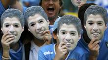 Fans of Uruguay pose with masks of Luis Suarez before their 2014 World Cup round of 16 game against Colombia at the Maracana in Rio de Janeiro June 28, 2014. (Reuters)