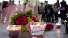 Flowers and candles are seen as people gather at a memorial honouring teen Amanda Todd in Maple Ridge, B.C., on Oct. 15, 2012. (Jonathan Hayward/The Canadian Press)