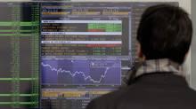 A man checks stock indexes on a screen of a bank in Milan, Italy, Monday, Nov. 28, 2011. (Luca Bruno/AP)