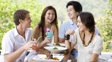 Four young adults enjoying a meal together (Photos.com/Photos.com)