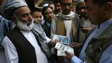 Exchanging dollars for Iranian rials in Herat, Afghanistan, in October. Sanctions have bitten deeply into Iran's oil exports, and the rial has dropped dramatically in value, prompting Tehran to ban the importation of some luxury goods. (REUTERS)