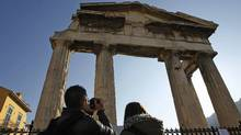 Tourists stand outside the closed gate of the Roman Agora during a 24-hour strike in Athens, Thursday, Dec. 1, 2011. (Thanassis Stavrakis/Thanassis Stavrakis/AP)