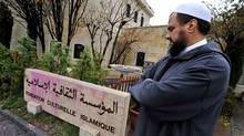 Imam at the Geneva mosque, Youssef Ibram, inspects the vandalised sign of the Islamic Cultural Foundation in Geneva on Nov. 30, 2009. (FABRICE COFFRINI/AFP/Getty Images)