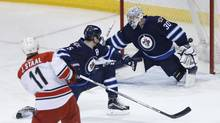 Carolina Hurricanes' Jordan Staal (11) scores on Winnipeg Jets goaltender Connor Hellebuyck (30) as Mark Stuart (5) defends during first period NHL action in Winnipeg on Friday, February 5, 2016. (JOHN WOODS/THE CANADIAN PRESS)