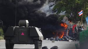 A Thai armoured personnel carrier moves toward a burning anti-government barricade.