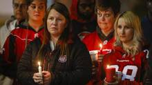 Mourners gather at a candle light vigil for murdered Stampeders player Mylan Hicks in Calgary, Alta., on Sept. 28, 2016. (Jeff McIntosh/THE CANADIAN PRESS)