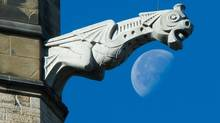 The moon is seen past a gargoyle on the Peace Tower of Parliament Hill in Ottawa on Friday, October 25, 2013. (Sean Kilpatrick/THE CANADIAN PRESS)