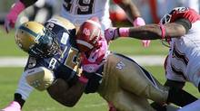 Calgary Stampeders' Malik Jackson (11) strips the ball from Winnipeg Blue Bombers' Chad Simpson (5) during first half CFL action in Winnipeg on Saturday, October 13, 2012. (John Woods/THE CANADIAN PRESS)