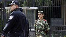 Chinese police officer patrols past a paramilitary policeman stand guard outside the Japanese Embassy in Beijing (Andy Wong)