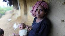 A woman from Myanmar holds her child in front of her makeshift home in an unregistered Rohingya refugee camp in Teknaf on June 17, 2012. (ANDREW BIRAJ/REUTERS)