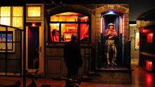 A visitor to the National Gallery in London views an installation by U.S. artists Ed Kienholz and Nancy Reddin Kienholz of a seedy reconstruction of Amsterdam's Red Light District. (TOBY MELVILLE/REUTERS)