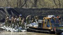 Canadian Forces members reinforce a dike along the Assiniboine River, at Poplar Point, Man., on May 15, 2011. (Ryan Remiorz/The Canadian Press/Ryan Remiorz/The Canadian Press)