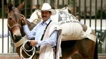 "Carlos Castaneda, 39, who was named Colombia's new Juan Valdez in 2006, poses with ""Conchita"" in Bogota (DANIEL MUNOZ/REUTERS)"