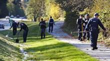 RCMP officers, police from local detachments and Surrey city workers comb the brush along a roadway in the Green Timbers Urban Forest on Oct. 23, 2007, as they search for evidence near a building where six men were found dead in Surrey, B.C. (Jeff Vinnick for The Globe and Mail)