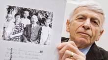 Auschwitz survivor and plaintiff Max Eisen holds a photo of himself and his Hungarian Jewish family before their deportation during the Holocaust, as he waits for the third day of the trial of former Nazi death camp officer Oskar Groening on April 23, 2015 at the Courthouse in Lueneburg, northern Germany. (JULIAN STRATENSCHULTE/AFP/Getty Images)