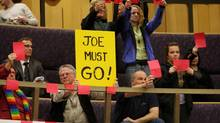 Protesters hold signs and red cards that signify a foul and an ejection (as in soccer) during the debate on a motion asking London Mayor Joe Fontana to take a leave of absence with pay until final disposition of the criminal charges against him in London, Ontario, Tuesday, December 11, 2012. The motion was defeated by a council vote of 8-5. (Dave Chidley/THE CANADIAN PRESS)
