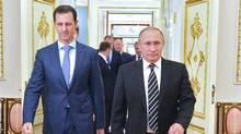 Russian President Vladimir Putin (R) greets his Syrian counterpart Bashar al-Assad upon his arrival for a meeting at the Kremlin in Moscow on October 20, 2015. (ALEXEY DRUZHININ/AFP/Getty Images)