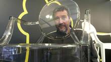 """Designer Philippe Starck looks through his Lucite """"Louis"""" chair, May 14, 2005, in New York during the Italian furnishings show """"i Saloni."""" (REUTERS)"""