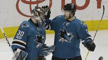 San Jose Sharks goalie Aaron Dell and defenseman Paul Martin celebrate after the Sharks defeated the Calgary Flames 3-1 in an NHL hockey game in San Jose, Calif., on April 8, 2017. (Jeff Chiu/AP)
