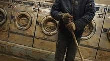 Eddie Liu uses a broom to clean up mud and water from extensive flooding in a laundromat due to superstorm Sandy in the Coney Island neighborhood of New York. (LUCAS JACKSON/REUTERS)