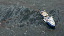 In this aerial photo taken in the Gulf of Mexico more than 50 miles southeast of Venice on Louisiana's tip, a boat with an oil boom tries to contain oil spilled from the explosion and collapse of the Deepwater Horizon oil rig, approximately seven miles from where the rig sunk, on Friday, April 23, 2010. (Gerald Herbert)