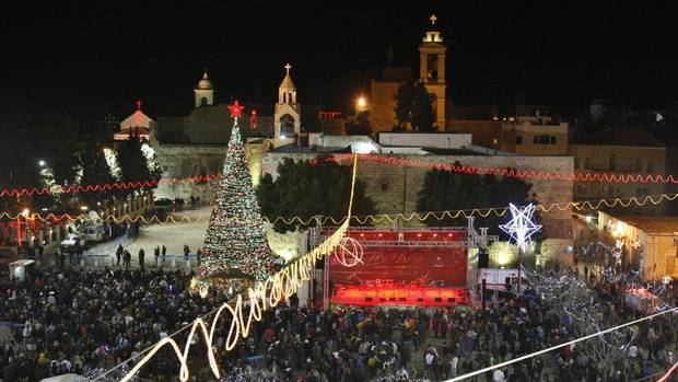 Christian worshippers and tourists celebrate at the Manger Square in front of the Church of the Nativity, in the West Bank town of Bethlehem, Monday, Dec. 24, 2012. (Adel Hana/AP)