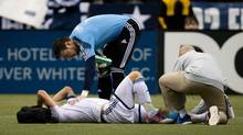 Vancouver Whitecaps' goalkeeper Joe Cannon, top, checks on injured teammate Jay DeMerit who had to be carried off the field during the first half of an MLS soccer game against Toronto FC in Vancouver, B.C., on Saturday March 2, 2013. (DARRYL DYCK/THE CANADIAN PRESS)