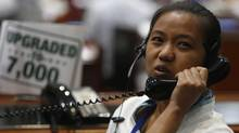 A Philippine Stocks Exchange trader takes orders on a telephone during trading in Manila's Makati financial district June 13, 2013. (ERIK DE CASTRO/REUTERS)