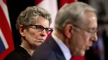 Ontario Premier Kathleen Wynne looks over at Energy Minister Bob Chiarelli during a press conference in Toronto on Oct 8, 2013, after the release of a report by the provinces's auditor-general on the costs related to the cancellation of an Oakville power plant. (MOE DOIRON/THE GLOBE AND MAIL)