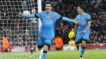 Barcelona's Lionel Messi, left, celebrates after scoring the second of two goals against Arsenal during Champions League play in London on Feb. 23. (Frank Augstein/AP Photo)