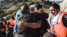 Syrian refugees react upon arrival on Lesvos island in Greece, after having crossed the Aegean sea from Turkey in an inflatable boat, on August 23, 2015. (ACHILLEAS ZAVALLIS/AFP/Getty Images)