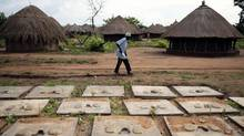 An elderly man uses a walking stick as he walks past concrete latrine covers at Okidi camp in Kitgum June 10, 2007. (EUAN DENHOLM/Reuters)
