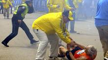 RACE DAY: Bill Iffrig, 78, is helped by an official after being knocked down near the finish line of the Boston Marathon, as police officers react to a second explosion seconds later. (Ken McGagh/AP)