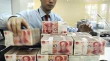 An employee counts Chinese yuan banknotes at a bank in Hefei, in China's Anhui province. (© Jianan Yu / Reuters/REUTERS)