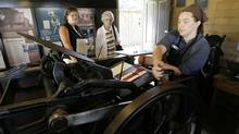 Rachel Klassen shows American tourists Lonnie Dressen, left, and Mildred Dickson how to operate the printing press at the Mennonite Heritage Village outside Steinbach, Man., on Aug 15, 2006. (John Woods)