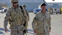 Task Force Kandahar commander Brigadier-General Jonathan Vance right, walks with then-incoming TFK commander Brigadier-General Daniel Menard after his arrival at Kandahar Air Field in November, 2009. (Master Corporal Angela Abbey)