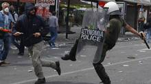 A protester clashes with a police officer in Athens' central Syntagma (Constitution) Square June 15, 2011. (YANNIS BEHRAKIS/REUTERS)